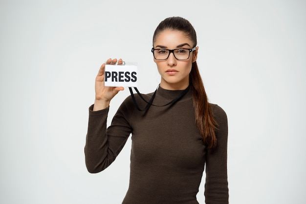Serious woman journalist showing press badge
