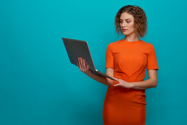 Serious woman keeping computer and typing