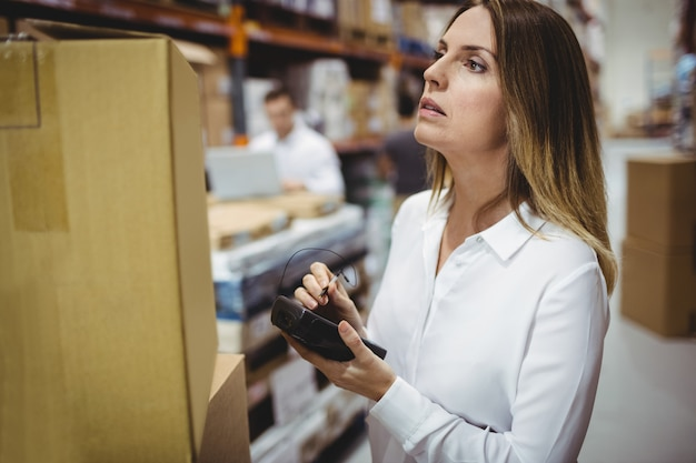 Serious woman looking at box in warehouse
