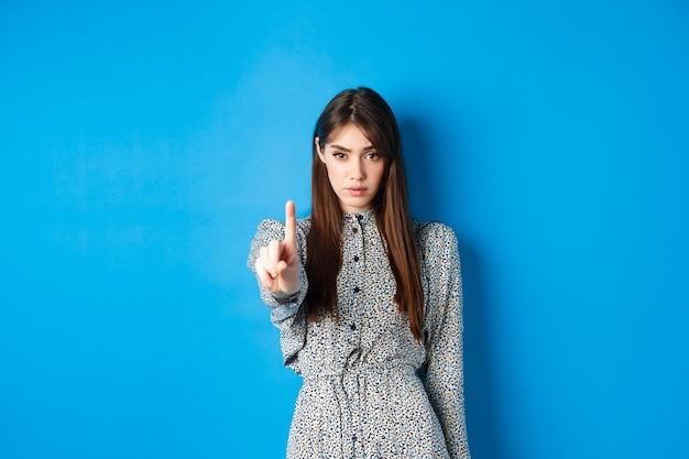 자신감이 넘치고 손가락을 흔드는 진지한 여자는 아니오라고 말하고, 당신을 멈추고, 동의하지 않고 반대하고, 파란색 드레스를 입고 서 있습니다.