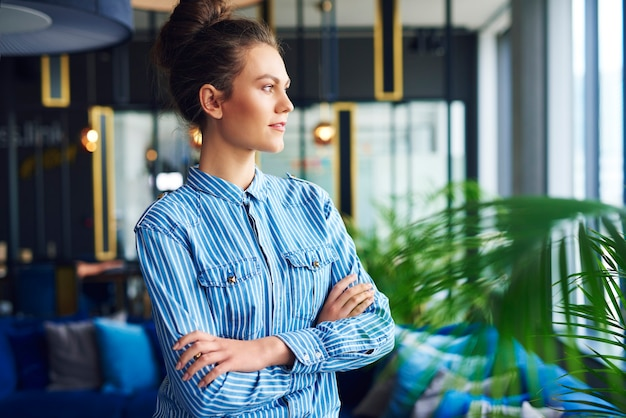Serious woman looking through window in the office