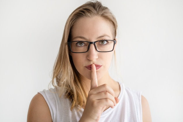 Serious woman making silence gesture and looking at camera