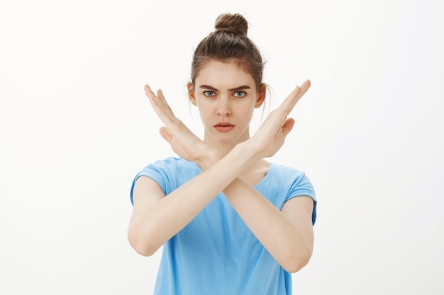 Serious woman making stop cross gesture, rejecting or forbidding something, disapprove action