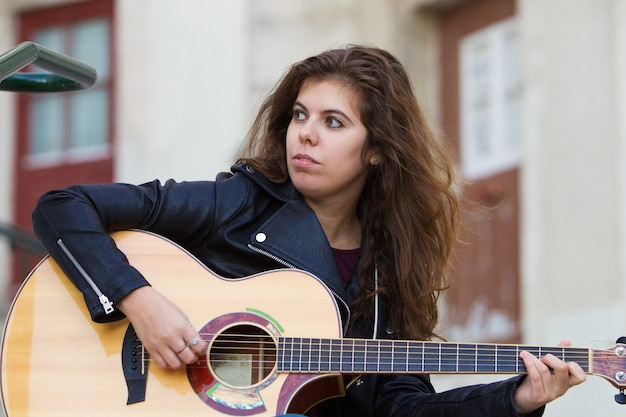Serious woman playing guitar on street stairs
