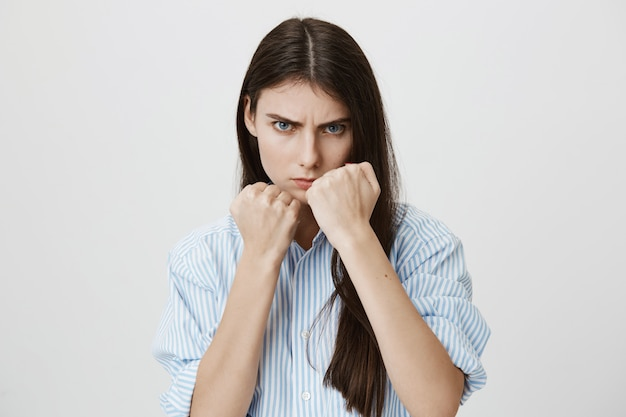 Serious woman raise hands in boxer pose, fighting