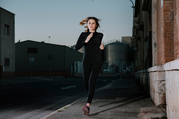 Serious woman running with determination on street