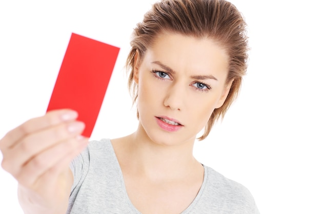 A serious woman showing a red card over white background