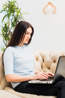 Serious woman sitting on couch with laptop