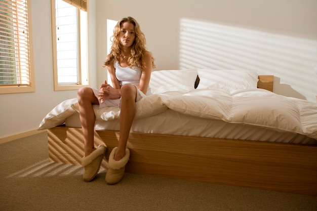Serious woman sitting on modern bed in bedroom in morning