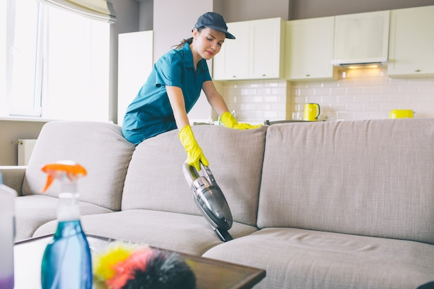 Serious woman stands and leans to sofa. she works with small vacuum cleaner. girl wears uniform and gloves.