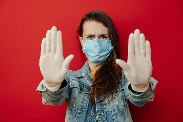 Serious woman in sterile face mask gloves, pulls hands towards camera in stop gesture, shows limit, wears denim jacket, isolated over on red background. quarantine pandemic coronavirus virus concept