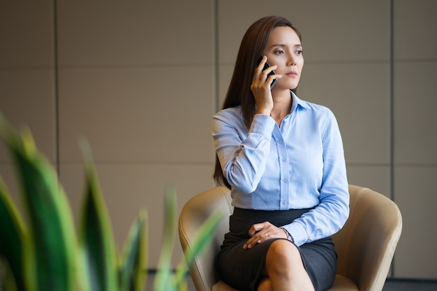 Serious woman talking on phone in office lobby Free Photo