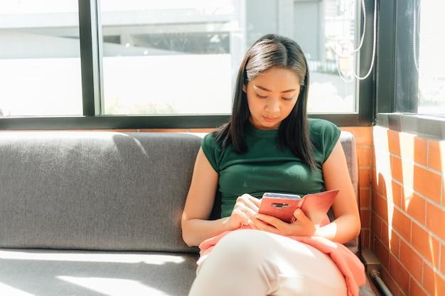 深刻な女性は、カフェの隅にあるソファーで自分のスマートフォンを使います。