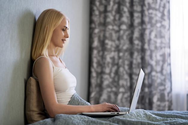 Серьезная женщина, использующая ноутбук, проверяет электронную почту онлайн, сидит на диване, ищет друзей в социальных сетях в интернете или работает на компьютере, пишет блог или смотрит веб-семинар, учится дома