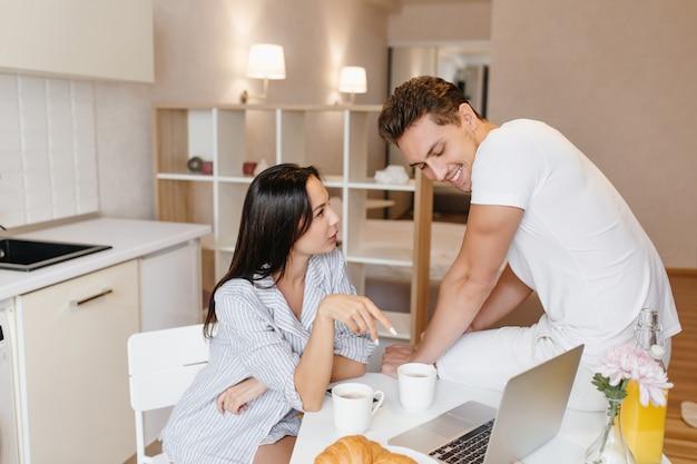 真面目な女性は台所で彼氏と話しているパジャマとして男性のシャツを着ています