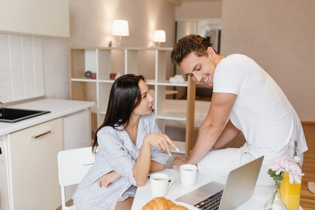 La donna seria indossa la camicia maschile come pigiama a parlare con il ragazzo in cucina