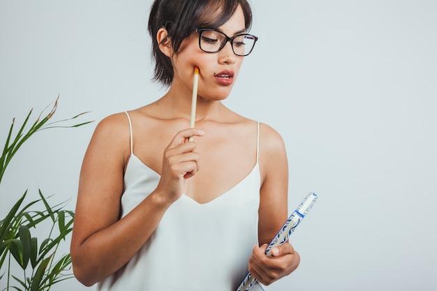 Серьезная женщина с карандашом на щеке