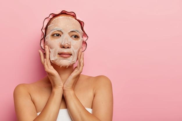 맨손으로 어깨를 가진 진지한 여성은 얼굴에 보습 페이퍼 마스크를 바르고, 뺨을 부드럽게 만지며, 부드럽고 건강한 피부를 가지고 있으며, 목욕 캡을 착용합니다.