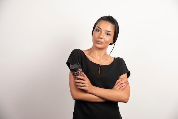 Серьезная женщина с чашкой кофе, стоящей на белой стене.
