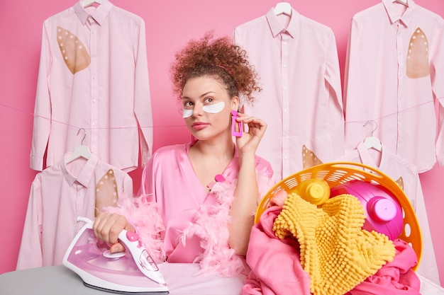 Serious woman with curly hair keeps hand on earring considers something wears dressing gown and beauty patches under eyes poses near ironing board with basket of laundry busy doing housework