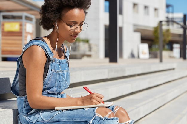 Serious woman with dark healthy skin, concentrated on writing essay, holds pen, makes notes in notepad, wears denim clothes, poses at stairs, listens audio book in earphones, poses at city view