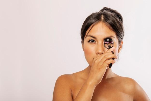 Serious woman with eyeñash curler