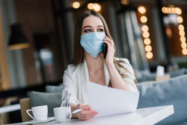 カフェテラスでニュースをチェックするスマートフォンを見ている保護フェイスマスクを持つ深刻な女性
