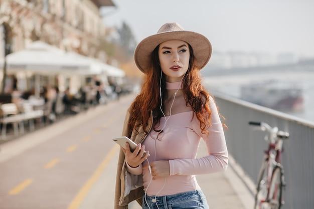 Серьезная женщина с волнистыми рыжими волосами ждет друга на набережной