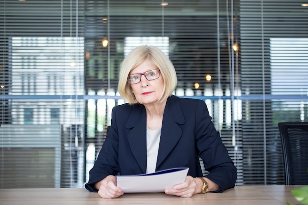 Serious woman working with documents in office