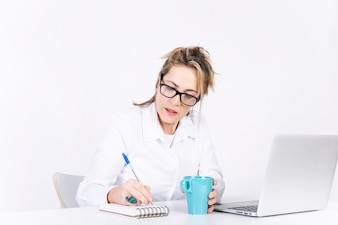 Serious woman writing in notebook near laptop