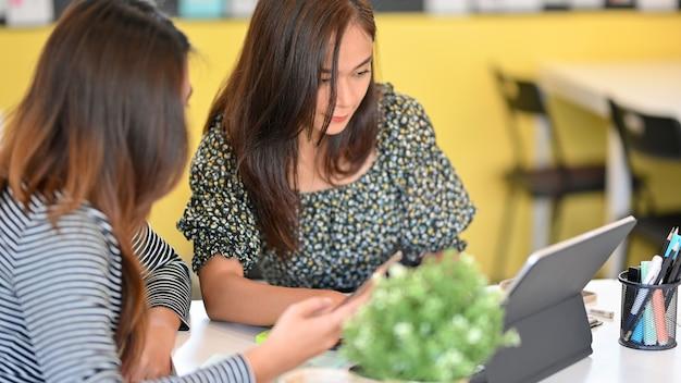 사무실에서 휴대용 태블릿을 사용하여 새로운 비즈니스 전략에 대한 아이디어를 공유하는 진지한 여성 동료