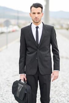 Серьезный работник, держа его портфель