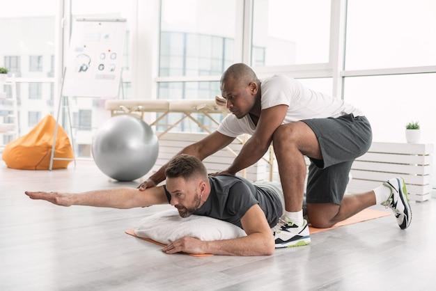심각한 운동. 바닥에 누워 신체 운동을하는 즐거운 젊은 남자