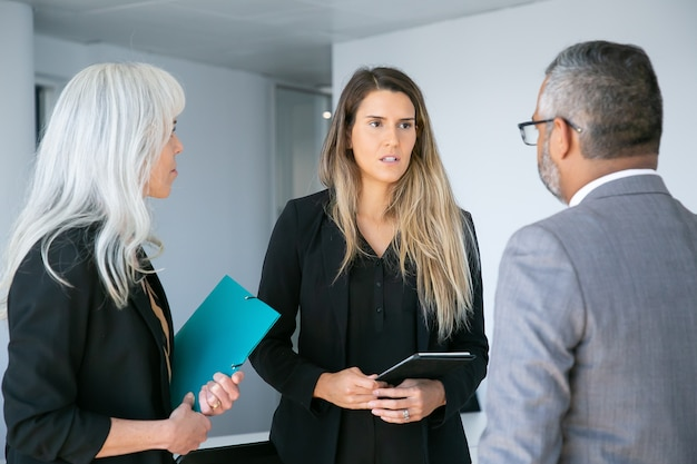 会社のceoにタブレットを報告している深刻な心配している女性マネージャー。ミディアムショット。ビジネスコミュニケーションの概念