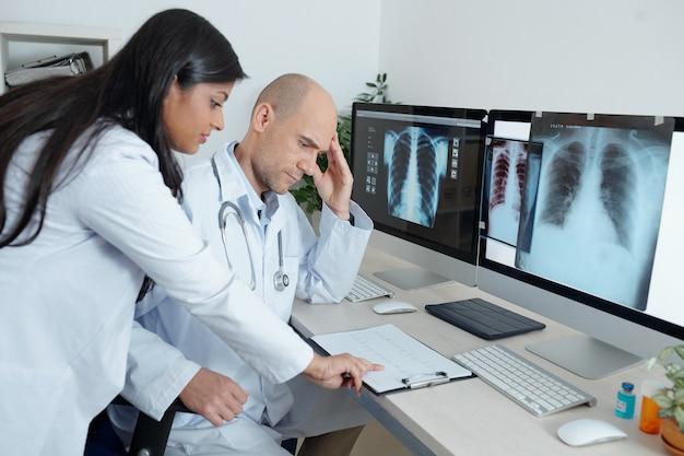 Серьезно обеспокоенные врачи общей практики смотрят на кардиограмму пациента, страдающего сердечными заболеваниями, перед ними на экранах находятся рентгеновские снимки его грудной клетки. Premium Фотографии