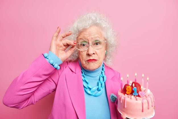 Серьезная морщинистая модница отмечает день рождения позами с тортом, одетая в стильный наряд, имеет яркий макияж, получает поздравления
