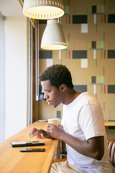 真面目な若いアフリカ系アメリカ人男性が共同作業スペースの机に座って、タブレットを使用して、画面に入力して読んでコーヒーを飲む