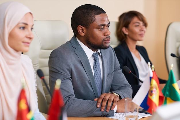 2人の異文化女性代表の間に座って外国人の同僚の1人に耳を傾ける深刻な若いアフリカ系アメリカ人のスピーカー