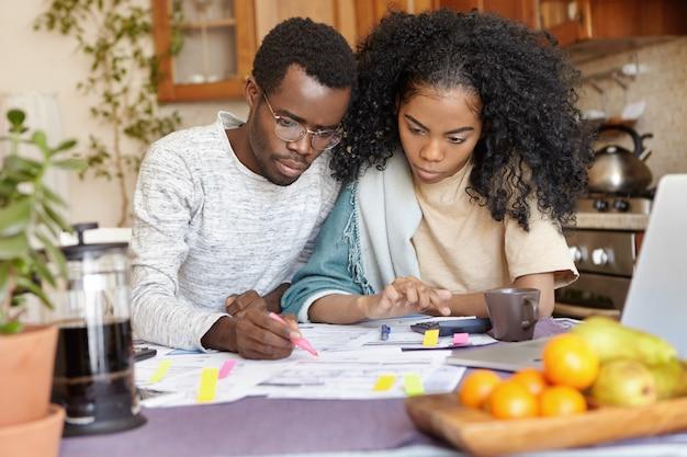 Grave giovane maschio africano con gli occhiali che tiene il pennarello, calcola le spese domestiche mentre gestisce il bilancio familiare insieme alla sua bella moglie, pianifica un grande acquisto e cerca di risparmiare denaro
