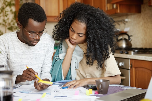 鉛筆と紙を保持しているガラスの深刻な若いアフリカ男性、紙幣とラップトップで台所のテーブルに座って、請求書を計算し、妻と一緒に家計を管理している