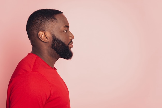 Serious young african man look empty space isolated over pink background
