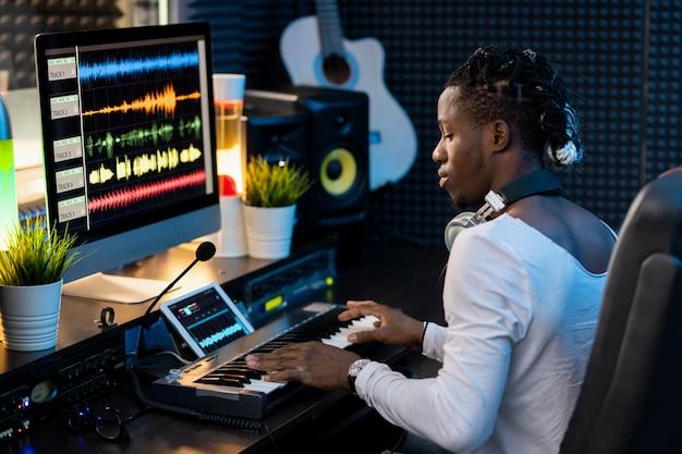 Серьезный молодой африканец нажимает клавиши на клавиатуре пианино и смотрит на дисплей планшета с визуализацией звука сигналов