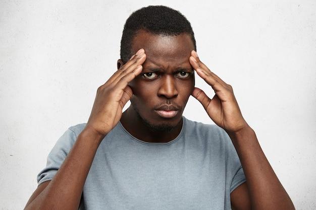 深刻な若いアフリカ系アメリカ人の男が頭に手をつないで、寺院を圧迫