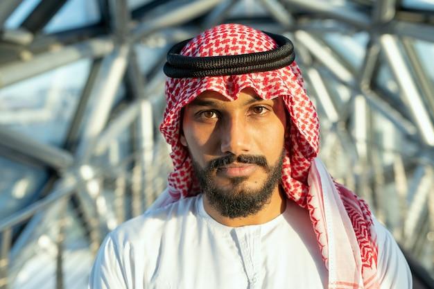 현대 비즈니스 센터 내부 카메라 앞에 서 있는 국가 복장을 한 진지한 젊은 아랍 남성 대표 또는 사업가
