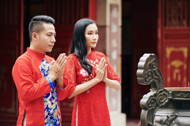 Serious young asian couple celebrating lunar new year and praying at ancient bronze urn with incense sticks at buddhist temple