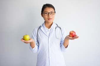 Serious young Asian female doctor holding red and yellow apple.