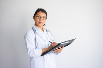 Serious young Asian female doctor writing medical prescription.