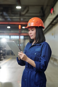 Serious young asian female engineer in overall analyzing industrial processes with tablet app at factory