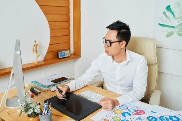 モバイルアプリケーションのロゴタイプまたはアイコンのセットを描く眼鏡の真面目な若いアジアのグラフィックデザイナー