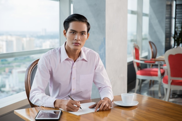 Serious young asian man writing in cafe